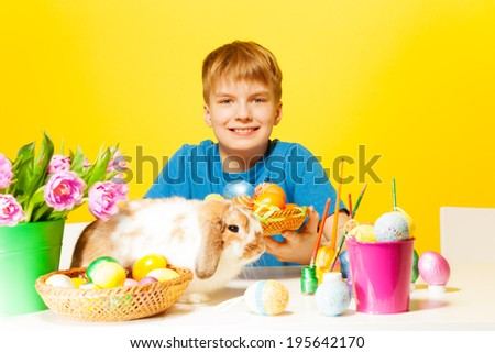 Smiling boys holds plate with Eastern eggs