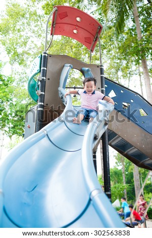 Smiling boys with bending knee on chute. Asian boy on the slide outdoors - stock photo