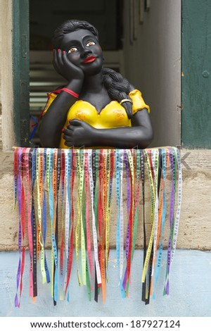 Smiling Brazilian woman colorful namoradeira figurine in the window decorated with wish ribbons fita do Bonfim Salvador Bahia Brazil - stock photo