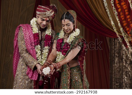 Smiling bride and bridegroom during traditional ceremony - stock photo