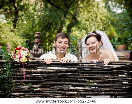 smiling bride and groom look out over the fence - stock photo