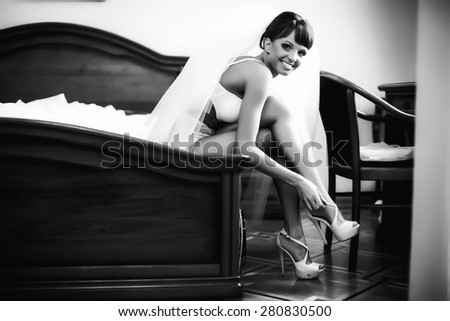 smiling bride is sitting and wearing high hils