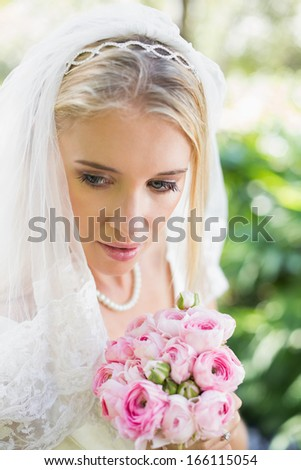 Smiling bride wearing veil holding bouquet looking down in the countryside