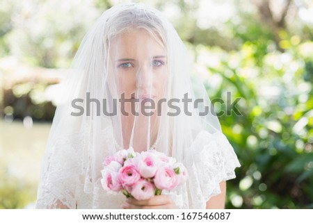 Smiling bride wearing veil over face holding rose bouquet in the countryside