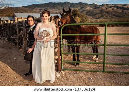 Smiling bride with same sex groom and horse