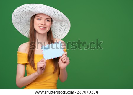 Smiling bright woman in summer dress and white hat showing blank envelope banner - stock photo