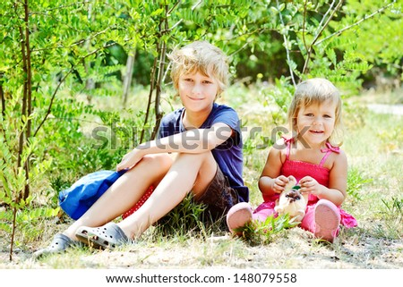 Smiling brother and little sister  in the garden - stock photo