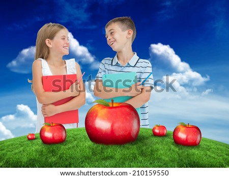 Smiling brother and sister holding their exercise books against green field under blue sky - stock photo