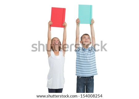 Smiling brother and sister holding their notebooks above their head while posing on white background - stock photo