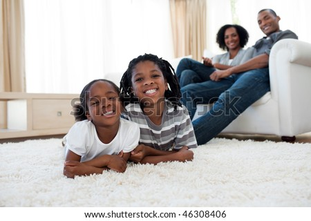 Smiling brother and sister lying on the floor  in the living room - stock photo