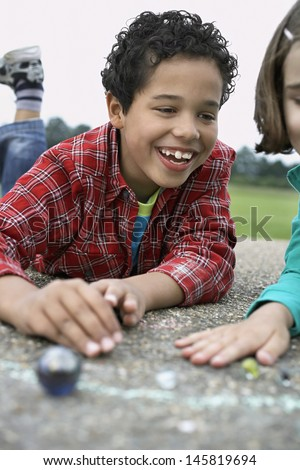 Smiling brother and sister playing marbles on playground - stock photo