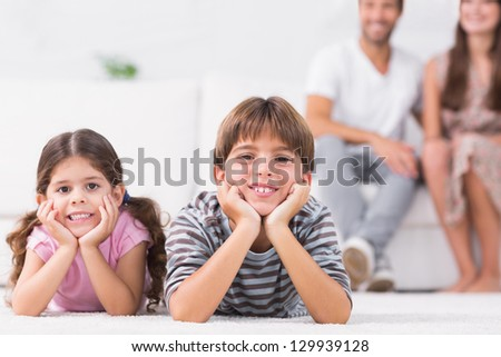 Smiling brother and sister with parents sitting behind them - stock photo