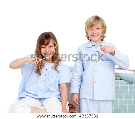 Smiling brother and siter brushing their teeth at home - stock photo