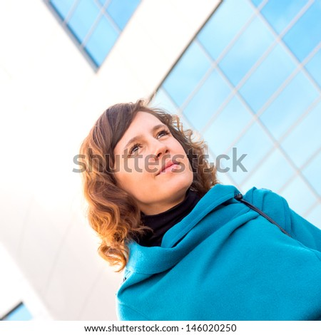 Smiling brunette beautiful business woman wearing blue suit outside portrait over glass wall (building). Vertical, copy space. - stock photo