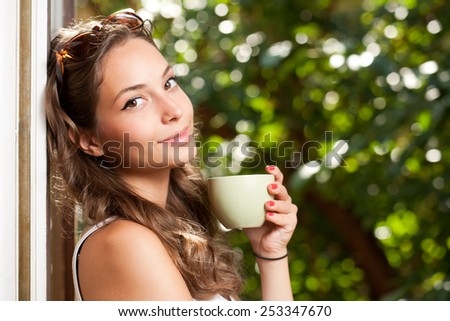 Smiling brunette beauty holding green cup with hot beverage.