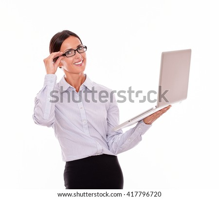 Smiling brunette businesswoman holding a laptop with a toothy smile while looking at the camera and wearing her straight hair back while she is touching her glasses with one hand, isolated - stock photo