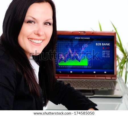 smiling brunette businesswoman in office with laptop - stock photo