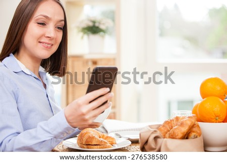 Smiling brunette businesswoman is having breakfast while checking her emails at home - stock photo