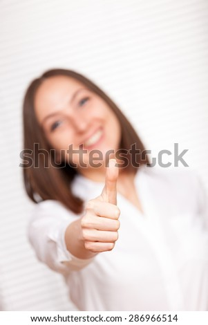 Smiling brunette businesswoman is making positive thumb gesture over white background - stock photo