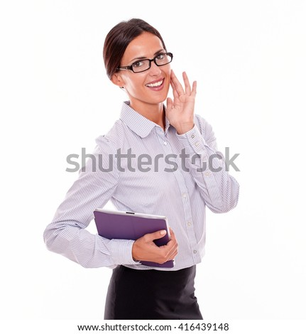 Smiling brunette businesswoman with glasses carrying a tablet, wearing her straight hair tied back and a button down shirt, looking at the camera with her left hand on her chin, on a white background - stock photo