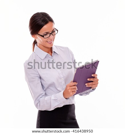 Smiling brunette businesswoman with glasses looking at a tablet, wearing her straight hair tied back and a button down shirt, with the tablet in both hands, on a white background - stock photo