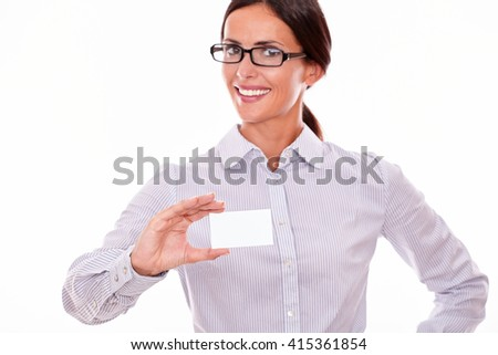 Smiling brunette businesswoman with glasses, wearing her long hair tied back, and a button down shirt, holding a blank visit card in one hand on a white background