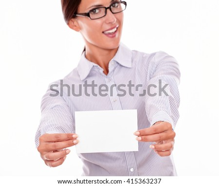 Smiling brunette businesswoman with glasses, wearing her long hair tied back, and a button down shirt, looking excited, holding a blank copy space with both hands in front of her