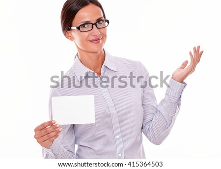 Smiling brunette businesswoman with glasses, wearing her long hair tied back, and a button down shirt, gesturing, holding a blank copy space in one hand on a white background
