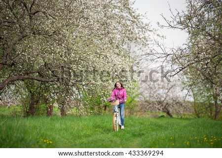 Smiling brunette female riding a vintage white bicycle with flowers basket, against the background of blooming trees, dandelions and fresh greenery in spring garden. - stock photo