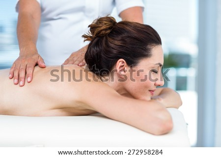 Smiling brunette getting back massage in a healthy spa - stock photo