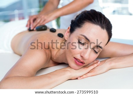 Smiling brunette getting hot stone massage in a healthy spa - stock photo