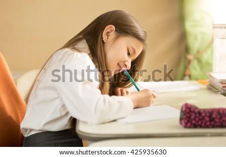 Smiling brunette girl in white shirt sitting behind desk and doing homework - stock photo
