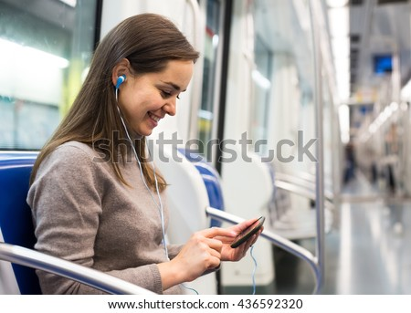 smiling brunette girl using cell phone and smiling at subway