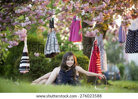 Smiling brunette girl with basket looking away sitting in the garden among colorful baby dresses hanging in the japanese cherry blossom tree, horizontal picture - stock photo