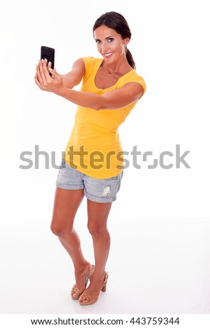 Smiling brunette holding a cell phone to take a selfie while looking at the camera and wearing a yellow t-shirt and short jeans isolated