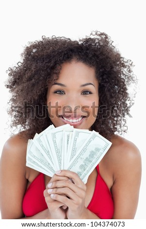 Smiling brunette holding a fan of bank notes against a white background