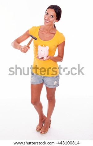 Smiling brunette holding a pink piggy bank and hammer gesturing while looking at camera and wearing a yellow t-shirt and short jeans isolated - stock photo