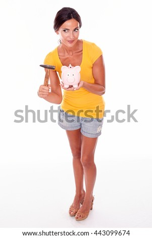 Smiling brunette holding a pink piggy bank and hammer gesturing while looking away secretively and wearing a yellow t-shirt and short jeans isolated