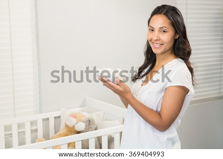 Smiling brunette holding baby shoes in bedroom