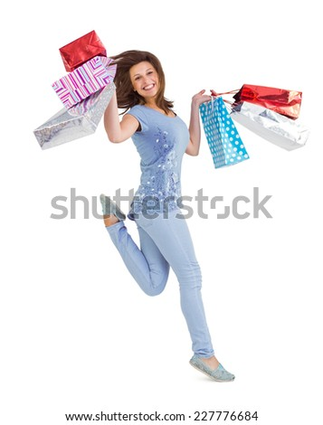 Smiling brunette jumping while holding shopping bags on white background - stock photo