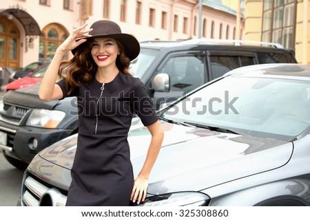 Smiling brunette near car - stock photo