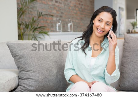 Smiling brunette on a phone call in living room - stock photo
