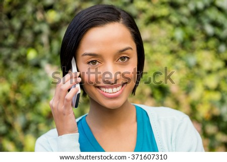 Smiling brunette on a phone call outdoors - stock photo