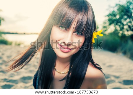 Smiling brunette outdoors front view looking at camera - stock photo