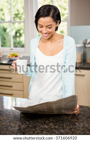 Smiling brunette reading newspaper and holding cup in the kitchen - stock photo