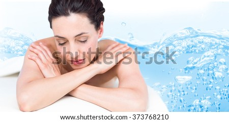 Smiling brunette relaxing on massage table against close up on blue sparkling water - stock photo