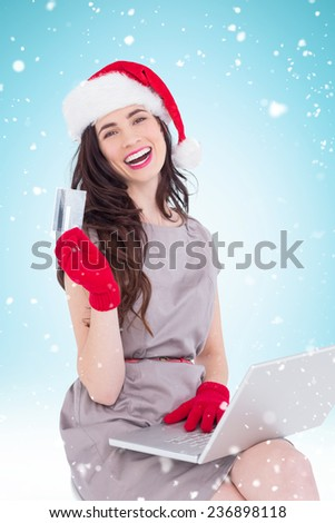 Smiling brunette shopping online with laptop against blue background with vignette - stock photo