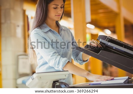 Smiling brunette student making a copy in library - stock photo