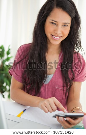 Smiling brunette student using a calculator to do her homework - stock photo