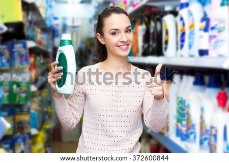 Smiling brunette woman choosing detergent in laundry section of supermarket - stock photo
